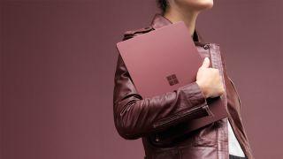 Woman carrying Microsoft Surface Laptop